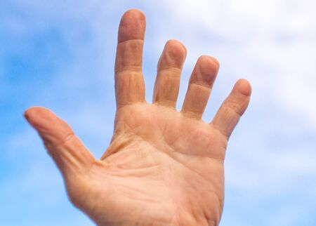 Male hand with clipped fingers against the blue sky . Stock Photo