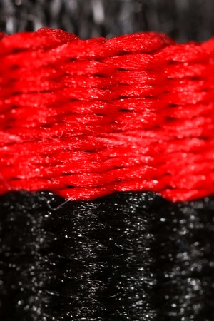 Black and red thread on fabric. Macro