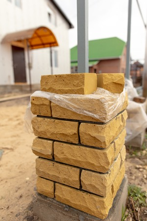 unfinished brick pillar at the construction site .
