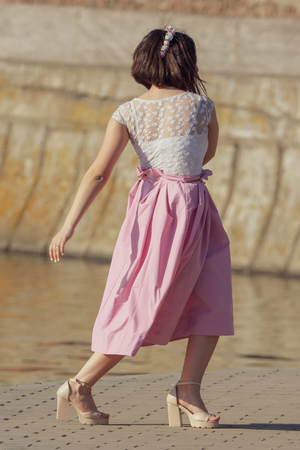 A girl in high heels near the embankment .