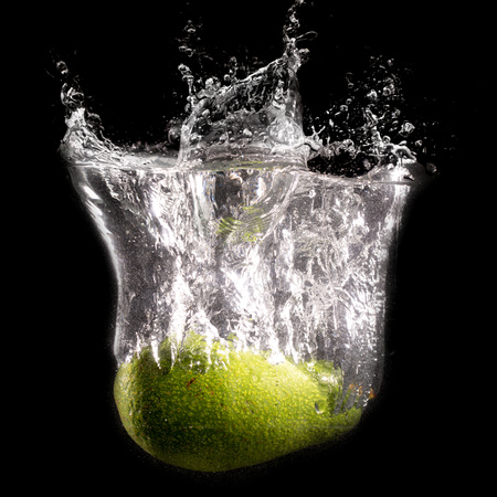Green avocado in water on a black background .