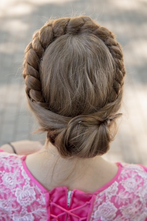 Round braid of hair on the head of a girl .