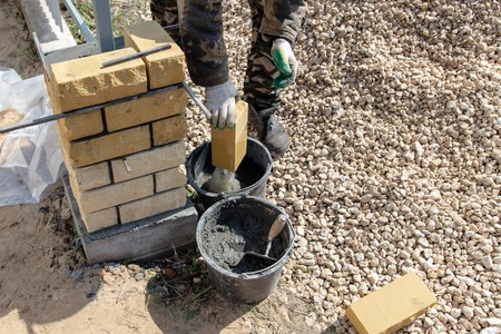 man builds a brick wall at a construction site .
