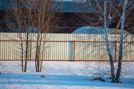 Fence on the site in the village in winter .