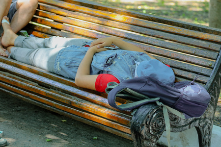 the girl is sleeping on a park bench . Stock Photo