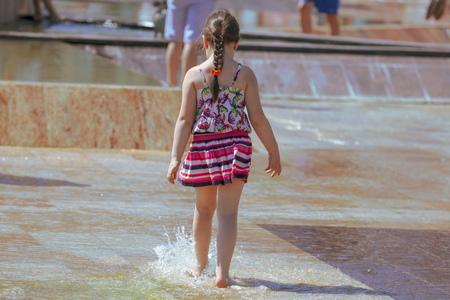 Ragazza che salta in acqua in una fontana.