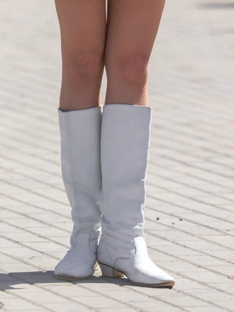 Legs of a girl in white leather boots .