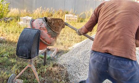 Il lavoratore impasta il calcestruzzo in un cantiere edile.