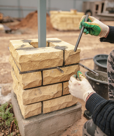 The worker is laying bricks on the fence .