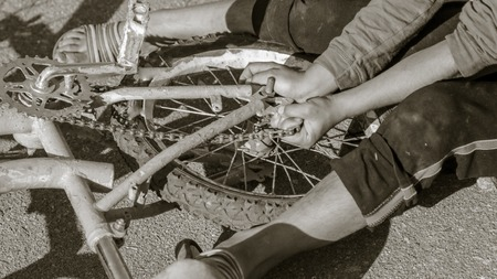 Boy repairing a bike on the road . Imagens
