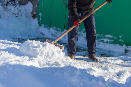 Man cleans the road from snow in winter .