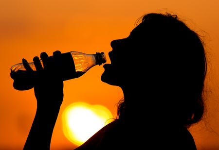 Silhouette of a girl drinking water at sunset .