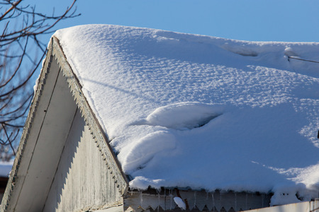 Snow on the roof of the house in winter . Imagens