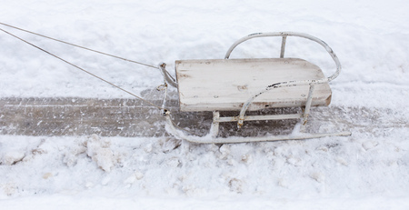 Old wooden sled in the snow in winter .
