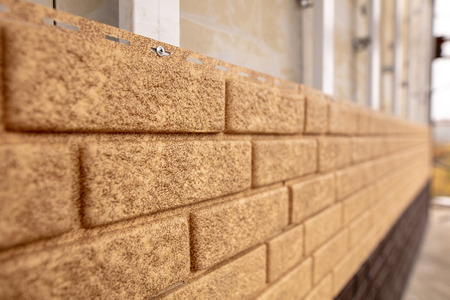 Installing siding on the wall of the house under the brick . Stock Photo - 112089339