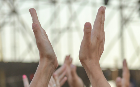 Hands raised up by a man at a concert .