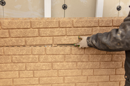Installing siding on the wall of the house under the brick . Stock Photo - 112172735