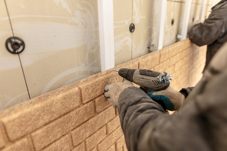 Installing siding on the wall of the house under the brick .