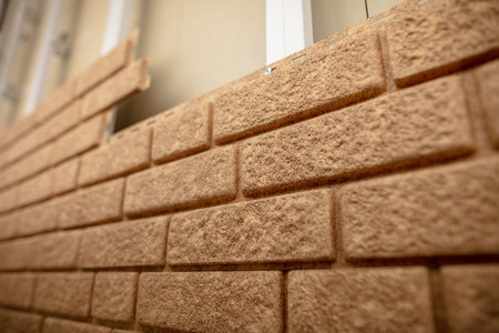 Installing siding on the wall of the house under the brick . Stock Photo - 118823102