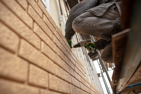 Installing siding on the wall of the house under the brick . Stock Photo - 118824564