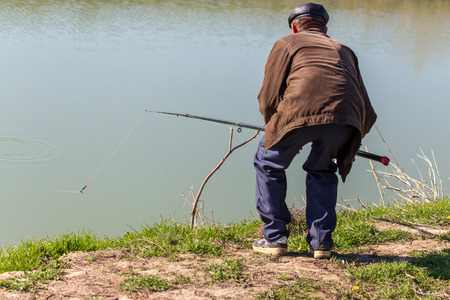 A man with a fishing rod is fishing on the river bank . Banque d'images