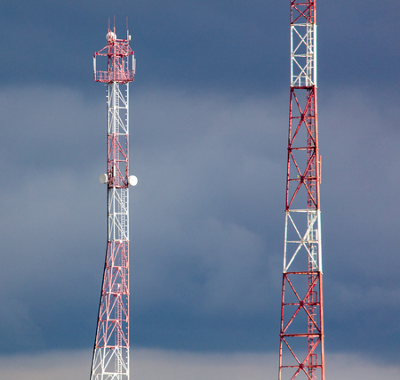 Metal tower for the transfer of tv on the background of clouds .