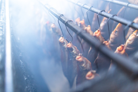 Salted fish is smoked on hooks in the smokehouse