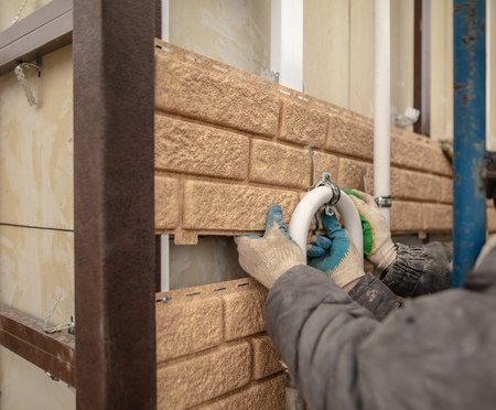 Installing siding on the wall of the house under the brick . Stock Photo - 113845461