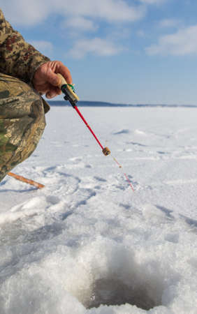 Man catches fish on ice in winter .