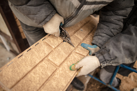 Installing siding on the wall of the house under the brick . Stock Photo - 113825185