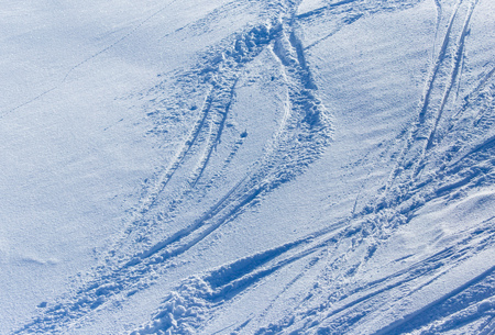 Traces of skiers on white snow in the mountains .