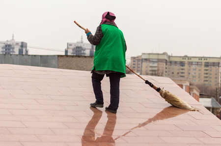 A cleaning lady is sweeping the road with a broom . Foto de archivo