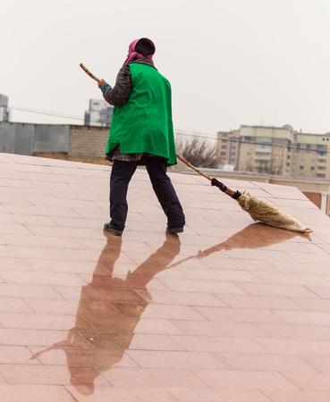 Eine Putzfrau fegt mit einem Besen die Straße.
