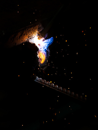Flame of fire and sparks from welding metal at night .