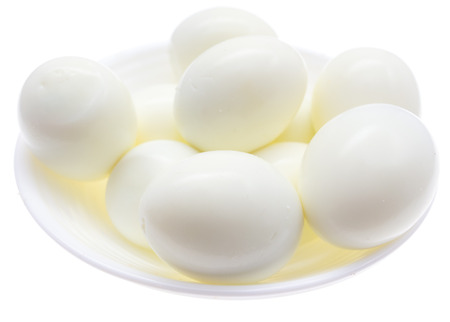 Peeled boiled eggs in a plate on a white background .