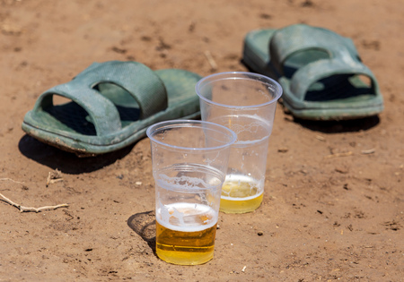 Beer in two plastic glasses near the shoes on the ground .
