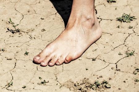 Girls bare feet on dry ground .