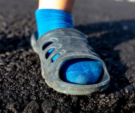 Feet of a boy on a new asphalt road .