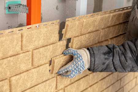 Installing brick siding on the wall of the house . Stock Photo - 119290531