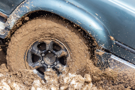 Car wheel slips in the dirt in nature .
