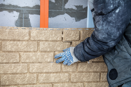 Installing brick siding on the wall of the house . Stock Photo - 119727325