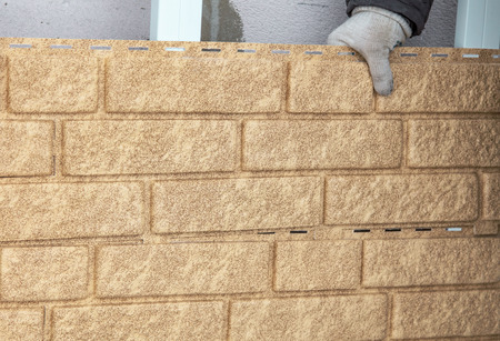 Installing brick siding on the wall of the house . Stock Photo - 119727231