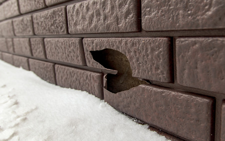 A hole on a broken siding on the wall of a house .