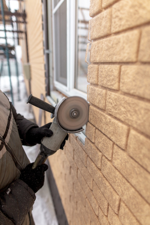 Installing brick siding on the wall of the house . Stock Photo - 119943556