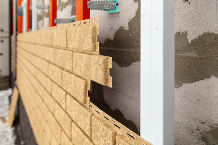 Installing brick siding on the wall of the house . Stock Photo - 119943620