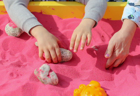 The child plays with his hands in the pink sand .