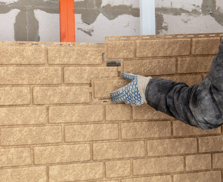 Installing brick siding on the wall of the house . Stock Photo - 119943731