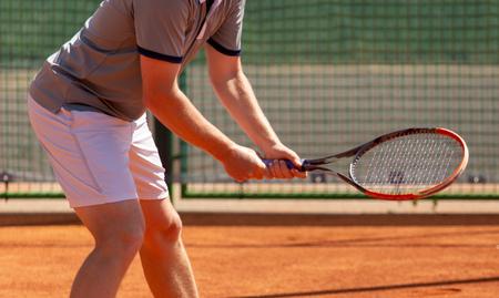 Ein Mann spielt Tennis auf dem Platz im Park.
