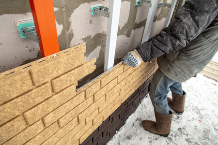 Installing brick siding on the wall of the house . Stock Photo - 120399196
