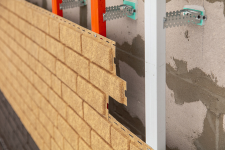 Installing brick siding on the wall of the house . Stock Photo - 120399349